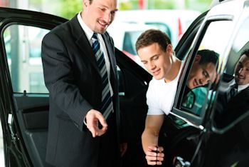 Men inspecting car with door open