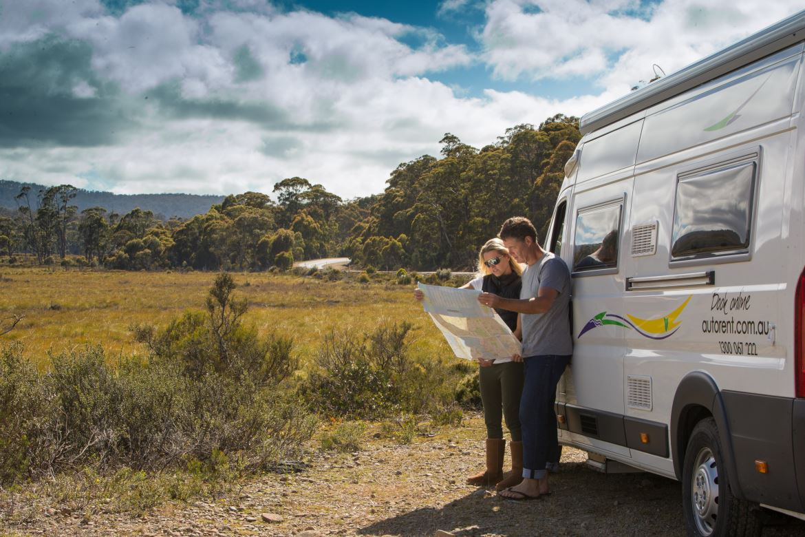 Couple reading map outside motorhome