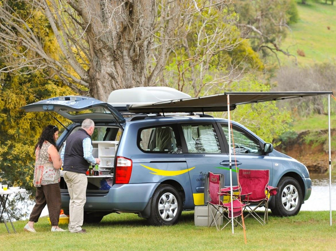 Two people standing at back of campervan