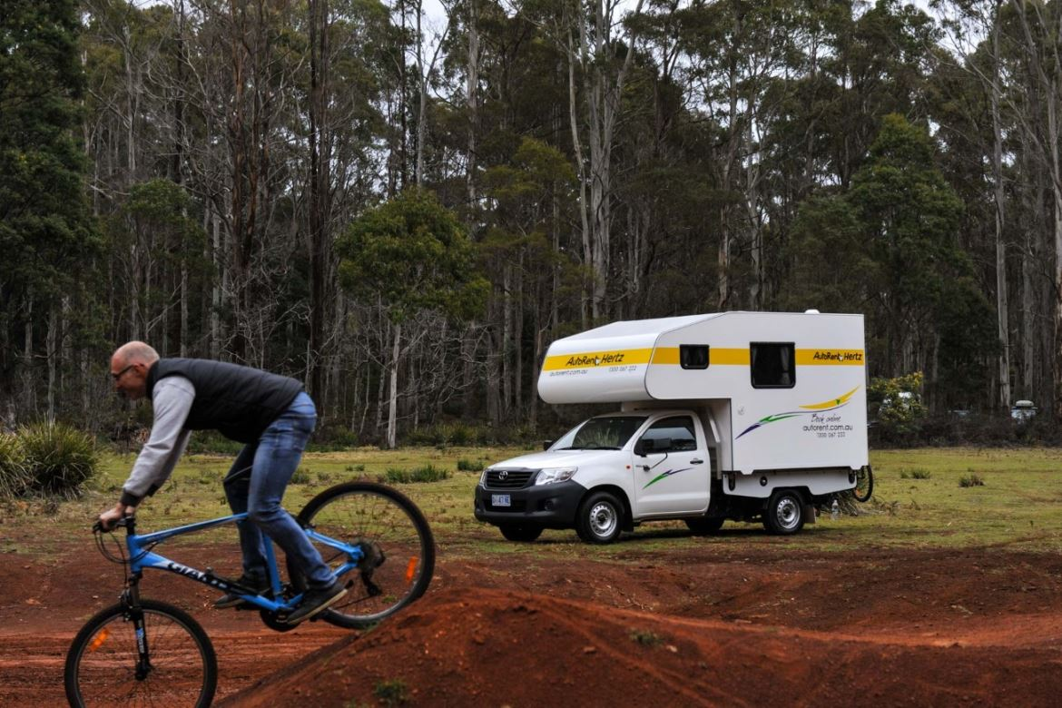 Person riding bike with 2 berth motorhome in background